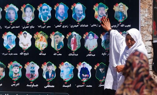 (AP Photo/Rafiq Maqbool). An Afghan woman cries as she touches a banner displaying photographs of victims of the Dubai City wedding hall bombing during a memorial service in Kabul, Afghanistan, Tuesday, Aug. 20, 2019. The deadly bombing at a wedding in...