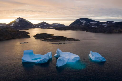 (AP Photo/Felipe Dana). In this Aug. 16, 2019, photo, large Icebergs float away as the sun rises near Kulusuk, Greenland. Scientists are hard at work, trying to understand the alarmingly rapid melting of the ice.