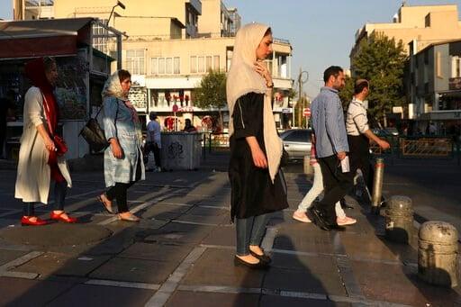 (AP Photo/Vahid Salemi). Pedestrians walk on a sidewalk in eastern Tehran, Iran, Monday, Aug. 19, 2019.