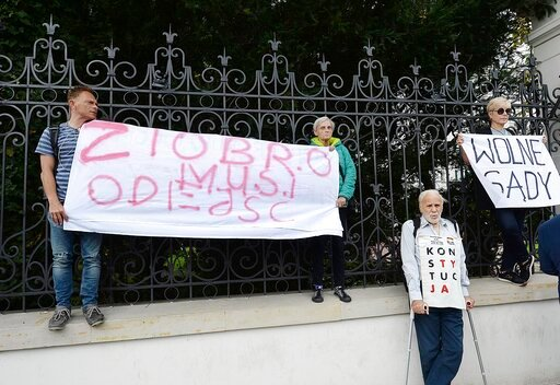 (AP Photo/Czarek Sokolowski). Protesters with banners calling on Justice Minister Zbigniew Ziobro to quit over allegations that his deputy encouraged an online hate campaign against defiant judges in Warsaw, Poland, Wednesday, Aug. 21, 2019. The deputy...