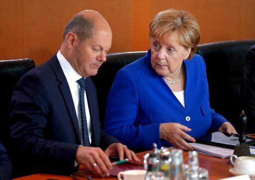 (AP Photo/Michael Sohn). German Chancellor Angela Merkel, right, and German Finance Minister Olaf Scholz, left, talk as they arrive for the weekly cabinet meeting at the Chancellery in Berlin, Germany, Wednesday, Aug. 21, 2019. The German government so...