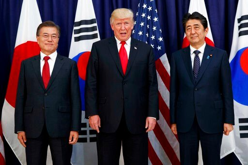 (AP Photo/Evan Vucci, File). FILE - In this July 6, 2017, file photo, U.S. President Donald Trump, center, meets with Japanese Prime Minister Shinzo Abe, right, and South Korean President Moon Jae-in before the Northeast Asia Security dinner at the U.S...