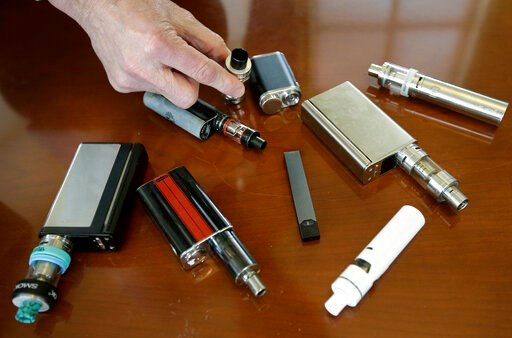 (AP Photo/Steven Senne). In this Tuesday, April 10, 2018 photo, Marshfield High School Principal Robert Keuther displays vaping devices that were confiscated from students in such places as restrooms or hallways at the school in Marshfield, Mass. Offic...