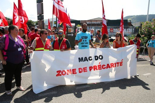"""(AP Photo/Bob Edme). Unionists demonstrate with a banner reading """"Mac Do, social insecurity zone"""" in front of a McDonald's restaurant, Thursday, Aug. 22, 2019 in Hendaye, southwestern France. The G-7 summit has for the first time co-opted the message o..."""
