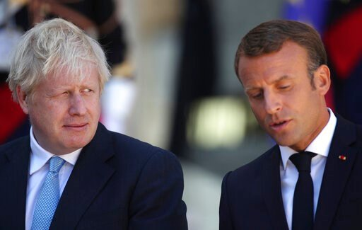 (AP Photo/Daniel Cole). Britain's Prime Minister Boris Johnson looks across at French President Emmanuel Macron at the Elysee Palace, Thursday, Aug. 22, 2019 in Paris. Boris Johnson traveled to Berlin Wednesday to meet with Chancellor Angela Merkel bef...