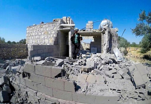 (Syrian Civil Defense White Helmets via AP). This photo provided by the Syrian Civil Defense White Helmets, shows a Civil Defense worker searching for victims from under the rubble of a destroyed building that was hit by airstrikes in the northern town...