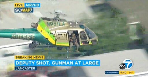 (KABC-TV via AP). This photo taken from video provided by KABC-TV shows a sheriff's department helicopter with a sniper in an open door searching for a gunman at large in Lancaster, Calif. on Wednesday, Aug. 21, 2019. The mayor of Lancaster says a depu...
