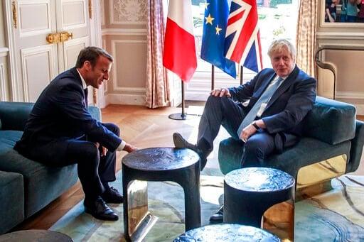 (Christophe Petit Tesson, Pool via AP). French President Emmanuel Macron, left, talks to Britain's Prime Minister Boris Johnson during their meeting at the Elysee Palace, Thursday, Aug. 22, 2019 in Paris. Boris Johnson traveled to Berlin Wednesday to m...