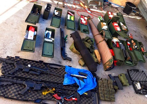 (Long Beach Police Department via AP). This undated photo released Wednesday, Aug. 21, 2019 by the Long Beach, Calif., Police Department shows weapons and ammunition seized from a cook at a Los Angeles-area hotel who allegedly threatened a mass shootin...