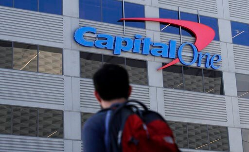 (AP Photo/Jeff Chiu, File). FILE - In this July 16, 2019, file photo, a man walks across the street from a Capital One location in San Francisco. Federal prosecutors say Paige Thompson, the woman accused of hacking Capital One and at least 30 other org...