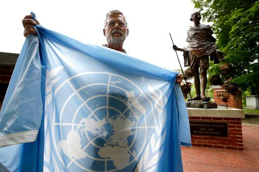 (AP Photo/Steven Senne). In this Wednesday, Aug. 21, 2019 photo, Lewis Randa, of Duxbury, Mass., displays a United Nations flag while standing near a bronze statue of Indian independence leader Mahatma Gandhi, behind right, at the Pacifist Memorial, in...