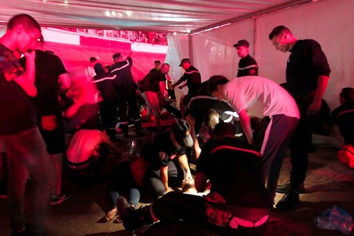 (AP Photo/Fateh Guidoum). People are being tended by rescue workers during Algerian rap artist Abderraouf Derradji's concert, known as Soolking, at a stadium in Algiers, Thursday, Aug. 22, 2019. The concert caused some deaths and injuries in a stampede...