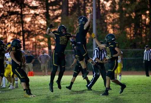 (AP Photo/Rich Pedroncelli). Paradise running back Lucas Hartley, center right, celebrates with teammate Kasten Ortiz after scoring the first touchdown of the year for the team in their high school football game against Williams, in Paradise, Calif., F...