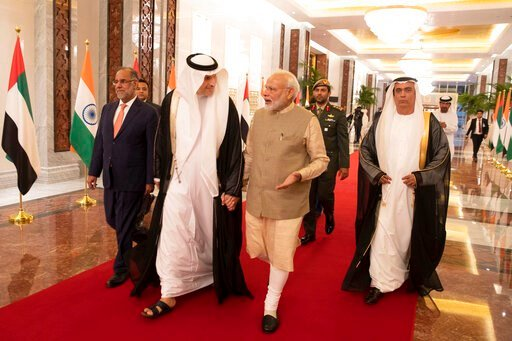 (WAM via AP). In this photo released by the state-run WAM news agency, Indian Prime Minister Narendra Modi, center right, walks with Khaldoon Khalifa al-Mubarak, chairman of the Abu Dhabi Executive Affairs Authority, center left, after arriving in Abu ...