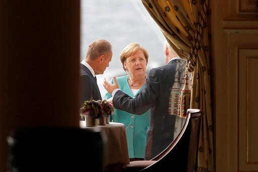 (AP Photo/Markus Schreiber, Pool). German Chancellor Angela Merkel, center, talks to President of the European Council Donald Tusk, left, and Britain's Prime Minister Boris Johnson during a G7 coordination meeting with the Group of Seven European membe...