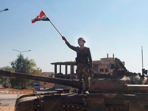 (AP Photo/Albert Aji). A Syrian soldier stands on a tank waving a national flag in the northwestern town of Khan Sheikhoun, Syria, on Saturday, Aug. 24, 2019.  The town was captured by Syrian troops this week after a monthslong offensive.