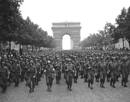 (AP Photo/Peter J. Carroll, File). FILE - In this Aug. 29, 1944 file photo, U.S. soldiers of Pennsylvania's 28th Infantry Division march along the Champs Elysees, the Arc de Triomphe in the background, four days after the liberation of Paris, France. T...