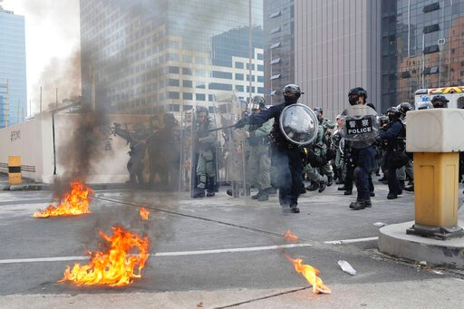 (AP Photo/Kin Cheung). Riot police gather around small fires during a protest in Hong Kong, Saturday, Aug. 24, 2019. Chinese police said Saturday they released an employee at the British Consulate in Hong Kong as the city's pro-democracy protesters too...