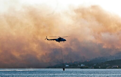 (AP Photo/Michael Svarnias). In this Saturday, Aug. 24, 2019 photo shows an helicopter fills its bucket with water during a wildfire near Pythagorio town on the eastern Greek island of Samos. Authorities evacuated two hotels and house the customers in ...