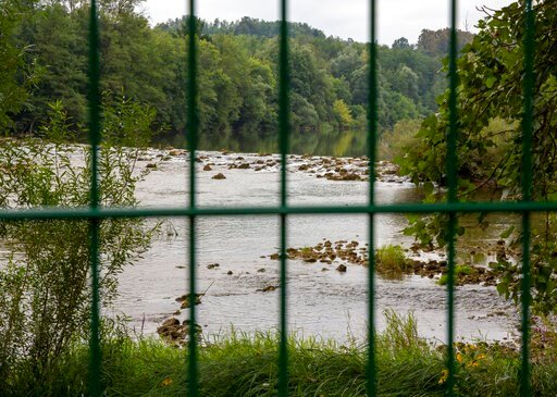 (AP Photo/Darko Bandic). In this photo taken Friday, Aug. 23, the Kupa river on the Slovenia-Croatia border is seen through the border fence in the village of Preloka, Slovenia. Police in Croatia say a migrant has died after a van carrying 12 of them p...