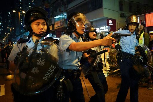 (AP Photo/Vincent Yu). Policemen pull out their guns after a confrontation with demonstrators during a protest in Hong Kong, Sunday, Aug. 25, 2019. Hong Kong police have rolled out water cannon trucks for the first time in this summer's pro-democracy p...
