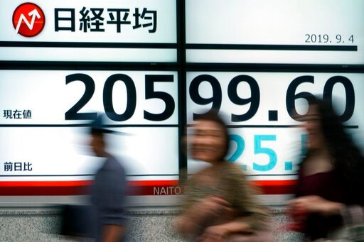 (AP Photo/Eugene Hoshiko). People walk past an electronic stock board showing Japan's Nikkei 225 index at a securities firm in Tokyo Wednesday, Sept. 4, 2019. Asian stock markets rose Wednesday following surprise weakness in U.S. manufacturing and wran...
