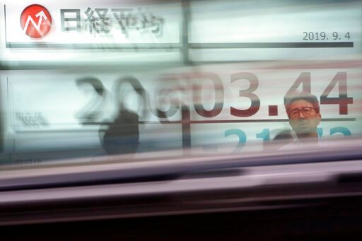 (AP Photo/Eugene Hoshiko). People stand in front of an electronic stock board showing Japan's Nikkei 225 index as a car goes by at a securities firm in Tokyo Wednesday, Sept. 4, 2019. Asian stock markets rose Wednesday following surprise weakness in U....