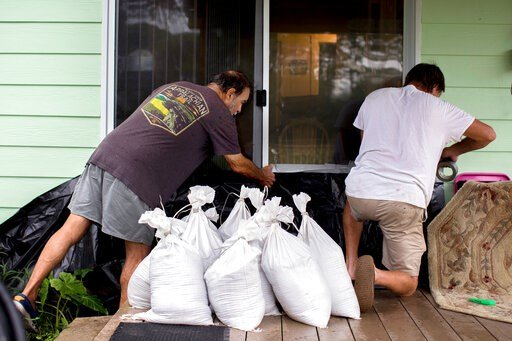 (AP Photo/Stephen B. Morton). Tony Pagan, left, helps a friend set sandbags in place over a plastic tarp on the back door as they prepare to evacuate before Hurricane Dorian arrives with its storm surge and tropical storm winds, Wednesday, Sept. 4, 201...