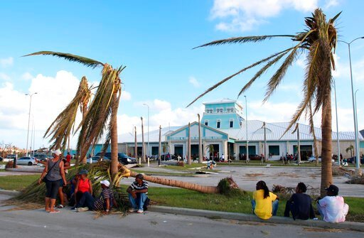 (AP Photo/Gonzalo Gaudenzi). People sit under broken palm trees outside the Leonard M. Thompson International Airport after the passing of Hurricane Dorian in Marsh Harbour, Abaco Islands, Bahamas, Thursday, Sept. 5, 2019. Thousands of desperate people...