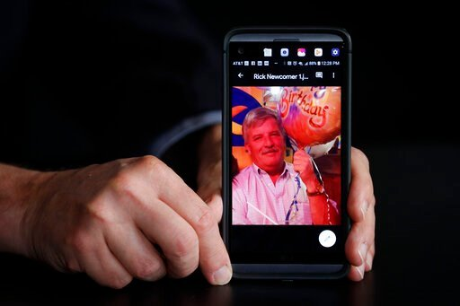 (AP Photo/John Minchillo). Larry Newcomer holds an image of his older brother Richard during an interview with The Associated Press, Monday, Aug. 26, 2019, in Cincinnati. Newcomer's older brother Richard was killed during a shooting in downtown Cincinn...