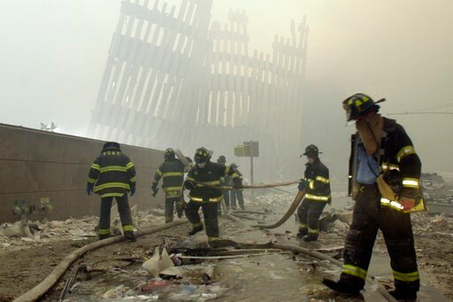 (AP Photo/Mark Lennihan). FILE - In this Sept. 11, 2001 file photo, firefighters work beneath the destroyed mullions, the vertical struts which once faced the outer walls of the World Trade Center towers, after a terrorist attack on the twin towers in ...