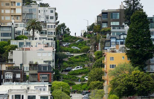 (AP Photo/Eric Risberg, File). FILE - In this April 15, 2019, file photo, cars wind their way down Lombard Street in San Francisco. Thousands of tourists could soon be forced to make reservations and pay to drive the famed crooked Lombard Street in San...