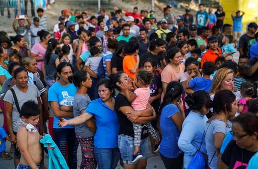 """(AP Photo/Veronica G. Cardenas). In this Aug. 30, 2019, photo, migrants, many who were returned to Mexico under the Trump administration's """"Remain in Mexico,"""" program wait in line to get a meal in an encampment near the Gateway International Bridge in ..."""