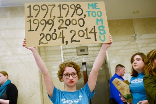 (Clarence Tabb Jr./Detroit News via AP, File). FILE - In this April 13, 2018 file photo, Morgan McCaul, 18, a survivor of Larry Nassar abuse, holds a sign showing the years that Larry Nassar was reported to Michigan State University as trustees arrive ...