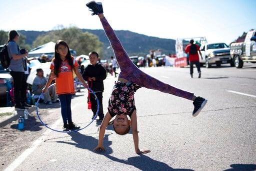 (Alma E. Hernandez/Gallup Independent via AP). In this Sept. 8, 2018 image, Tomica Johnson, 8, of Fort Defiance, Arizona, does cartwheels during the Navajo Nation Fair Parade near Tse Bonito, New Mexico.