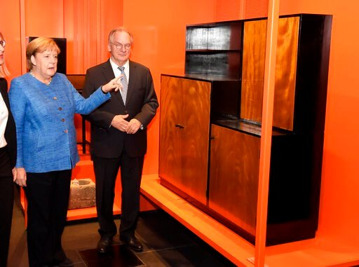 (AP Photo/Jens Meyer,Pool). German Chancellor Angela Merkel, left, and Reiner Haseloff, governor of the German state of Saxony-Anhalt, look at furniture during the official opening of the new Bauhaus Museum, built for the centenary of the founding of t...