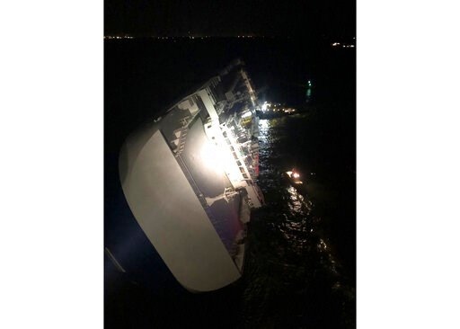 (U.S. Coast Guard via AP). In this photo provided by the U.S. Coast Guard, the Golden Ray cargo ship lists to one side near a port on the Georgia coast, early Sunday, Sept. 8, 2019. The ship, carrying vehicles, was being evacuated after sharply listing...