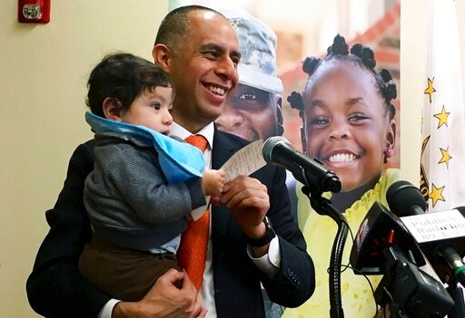 (Steve Klamkin/WPRO News via AP). In this March 20, 2019, photo, Mayor Jorge Elorza holds his son Omar during a news conference in Providence, R.I. Elorza's decision to frequently take his son to work with him has brought praise from some who say he's ...