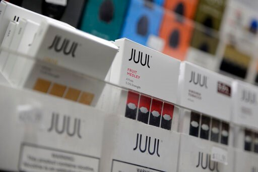 (AP Photo/Seth Wenig, File). FILE - In this Dec. 20, 2018, file photo Juul products are displayed at a smoke shop in New York. Federal health authorities say vaping giant Juul Labs illegally promoted its electronic cigarettes as a safer option to smoki...