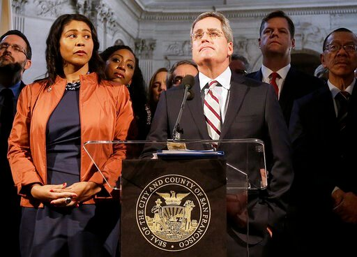 (AP Photo/Jeff Chiu, file). FILE - In this Dec. 12, 2017 file photo, city attorney Dennis Herrera, center, speaks at a news conference next to acting mayor London Breed, left, at City Hall in San Francisco. San Francisco officials are offering to buy P...
