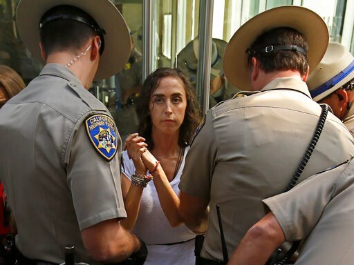 (AP Photo/Rich Pedroncelli). California Highway Patrol officers take into custody an opponent of recently passed legislation to tighten the rules on giving exemptions for vaccinations, after she cabled herself to the doors of the state Capitol in Sacra...