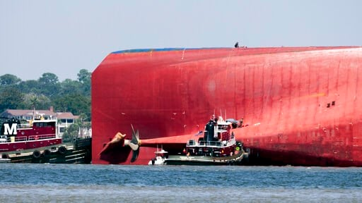 (AP Photo/Stephen B. Morton). Rescuers work near the stern of the vessel Golden Ray as it lays on its side near the Moran tug boat Dorothy Moran, Monday, Sept. 9, 2019, in Jekyll Island, Ga. Coast Guard rescuers have made contact with four South Korean...