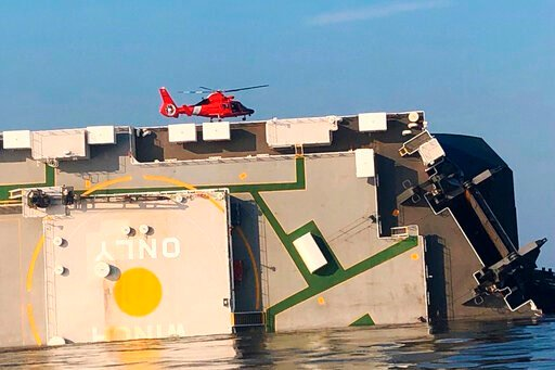 (U.S. Coast Guard via AP). In this image released by the U.S. Coast Guard, a USCG helicopter hovers over an overturned cargo ship in St. Simons Sound, Ga., Monday, Sept. 9, 2019. The U.S. Coast Guard says rescuers have heard noises from inside the ship...