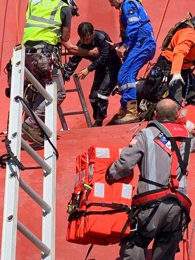 (U.S. Coast Guard via AP). In this image released by the U.S. Coast Guard, a crew member of the cargo ship Golden Ray is helped off the capsized ship Monday, Sept. 9, 2019, off St. Simons Island, Ga. A fire broke out aboard the ship early Sunday, listi...
