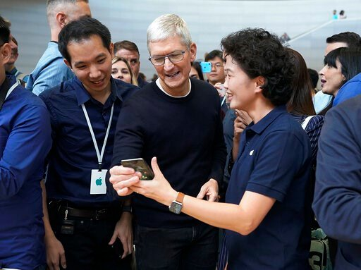(AP Photo/Tony Avelar). Apple CEO Tim Cook, center, looks at the the new iPhone 11 Pro Max, during an event to announce new products Tuesday, Sept. 10, 2019, in Cupertino, Calif.