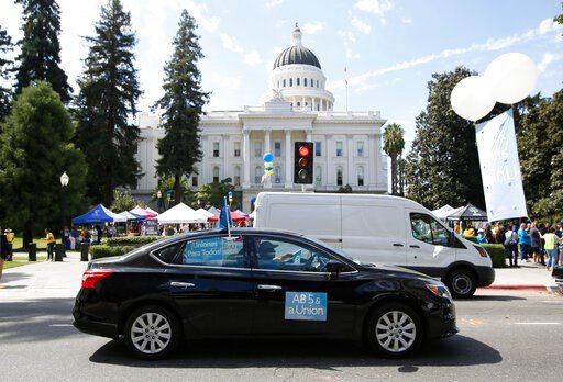 (AP Photo/Rich Pedroncelli). Dozens of supporters of a measure to limit when companies can label workers as independent contractors circle the Capitol during a rally in Sacramento, Calif., Wednesday, Aug. 28, 2019. If approved by the legislature and si...