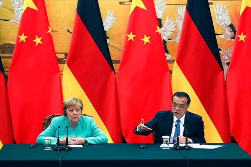 (Andrea Verdelli/Pool Photo via AP). Chinese Premier Li Keqiang gives a speech during the press conference at the end of the meeting with Chancellor of Germany Angela Merkel, left, at The Great Hall Of The People in Beijing, on Friday, Sept. 6, 2019.