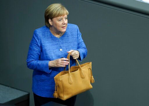 (AP Photo/Michael Sohn). German Chancellor Angela Merkel holds her bag as she arrives for a meeting of the German federal parliament, Bundestag, at the Reichstag building in Berlin, Germany, Wednesday, Sept. 11, 2019.