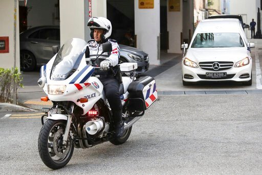 (AP Photo/Danial Hakim). A police motorcycle escorts a hearse, right, carrying the body of former Zimbabwe President Robert Mugabe leaving the Singapore Casket Funeral Parlour for the airport in Singapore Wednesday, Sept. 11, 2019. Mugabe died Friday, ...