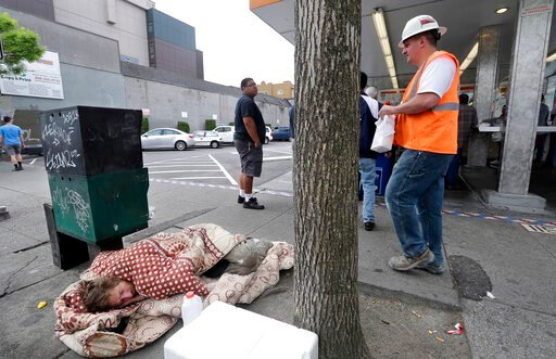 (AP Photo/Elaine Thompson, File). FILE - In this May 24, 2018 file photo, a man sleeps on the sidewalk as people behind line up to buy lunch at a Dick's Drive-In restaurant in Seattle. An elected official in King County, where Seattle is located, wants...